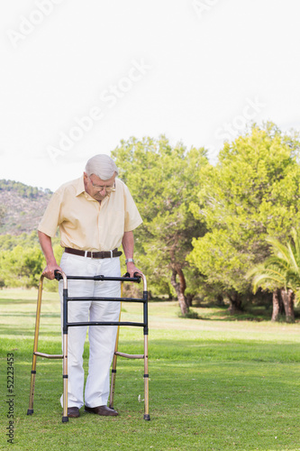 Elderly man using a zimmer frame to walk
