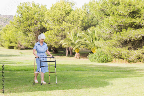 Elderly woman walking with a zimmer frame
