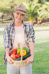 Pretty blonde carrying basket of vegetables