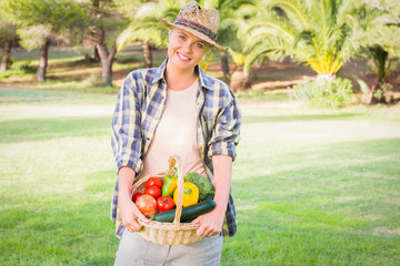 Pretty blonde carrying basket of home grown vegetables