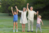 Smiling grandparents standing with their grandchildren cheering