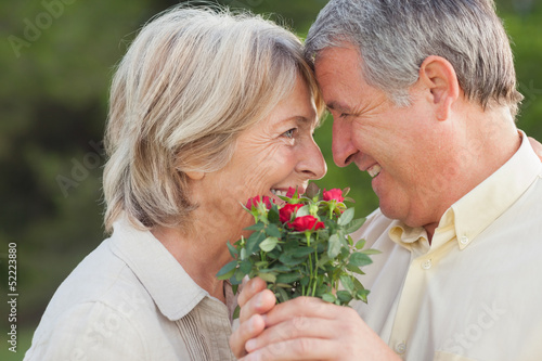 Older couple looking at each other and holding flowers
