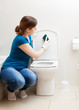 woman cleaning toilet seat with sponge