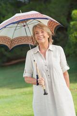 Smiling older woman holding umbrella