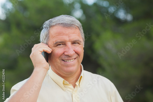 Grey haired man using his mobile portrait