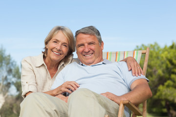 Portrait of older couple with man sitting in deck chair