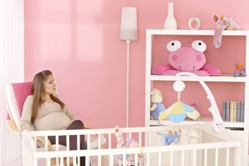 Pregnant mother sitting in baby's room