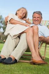 Older woman sitting on lap of smiling partner sitting in deck chair
