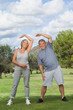 Mature woman and man stretching arms