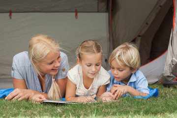 Mother and children reading on a sleeping bag