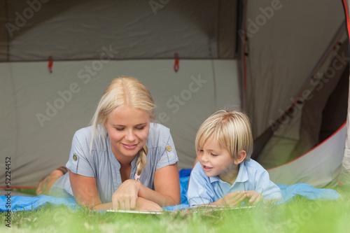 Mother and son reading on a sleeping bag