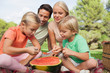 Happy family having watermelon at a picnic
