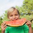 Cute blonde boy eating watermelon