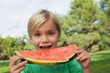 Cute blonde boy eating watermelon