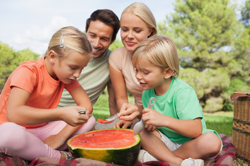 Happy family having watermelon at a picnic