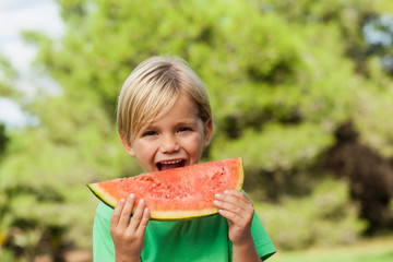 Cute happy boy eating watermelon