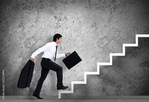 Businessman climbing the stairs to the top