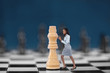 Businesswoman pushing chess piece