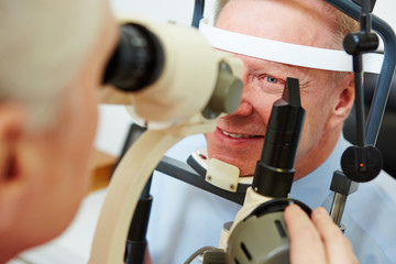 Senior man at optician looking in slit lamp