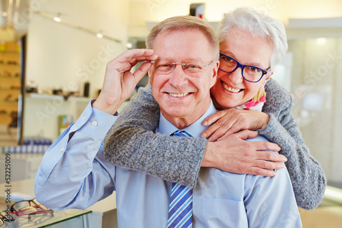 Happy senior couple with new glasses at optician