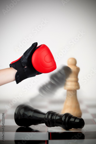 Hand of boxer knocking over chess piece