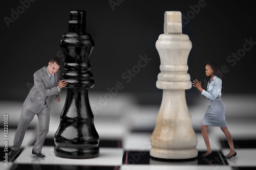 Businesspeople pushing chess pieces