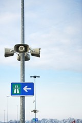 Loudspeaker on pole with hihgway sign