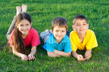 Three happy kids lying on the field
