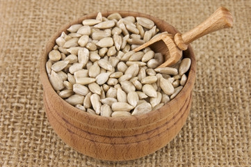 Shelled raw sunflower seeds in wooden bowl on burlap
