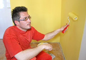 Young man painting, interior decoration