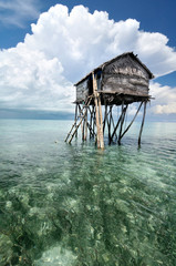 Bajau fisherman's wooden hut on sea water with blue sky