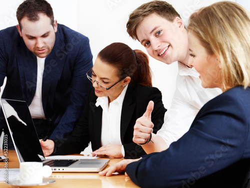 Business people are in a meeting, one shows thumb up