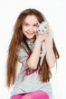 Portrait of a teenage girl with cat, on a gray background