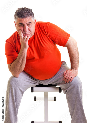 Overweight man sitting on a bench for abdominals, he takes a bre