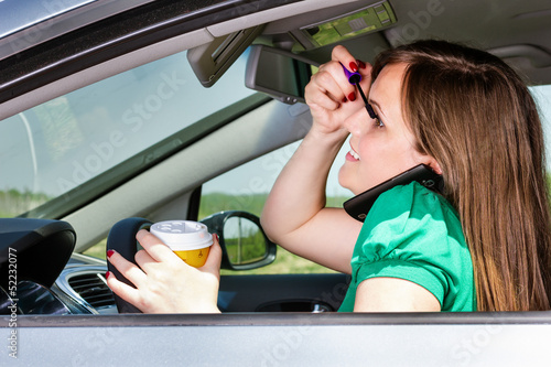 Pretty young woman applying makeup, speaking on phone and drinki