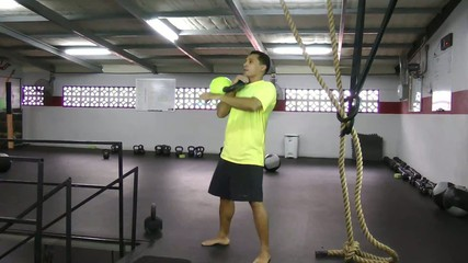 Athlete doing kettlebell clean and press crossfit exercise.