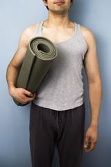 Young mixed race man carrying yoga mat