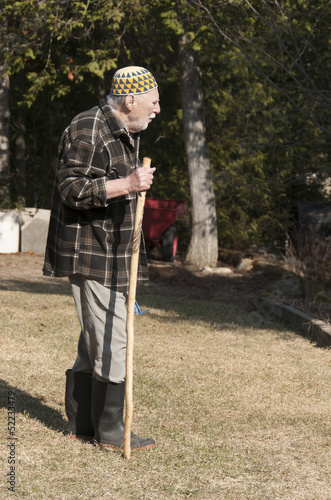 old man with kufi hat and stick walking on the garden