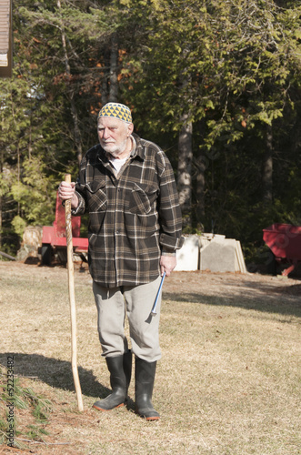 old man with kufi hat and stick looking at camera