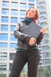 Beautiful redhead woman holding a laptop, at the street