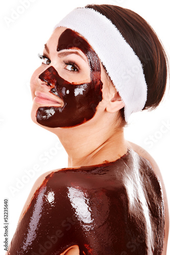 Young woman having chocolate facial mask.