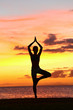 Yoga woman training in sunset in tree pose