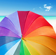 Colorful rainbow umbrella on a tropical beach