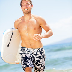Handsome man surfer fun on summer beach