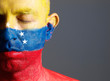 Man and his face painted with the flag of Venezuela and closed e