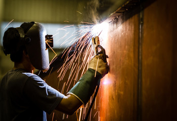 worker with protective mask welding metal and sparks