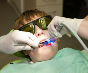 Boy in dental office during hardening of dental filling