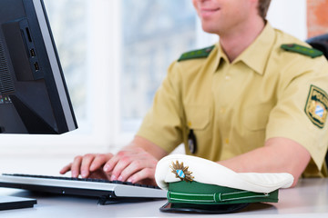 Polizist am Schreibtisch im Polizeirevier