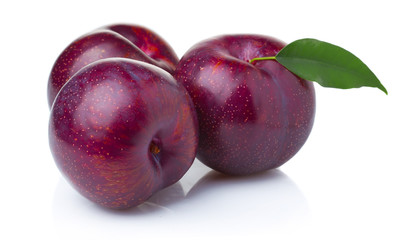 Three ripe purple plum fruits with green leaves isolated