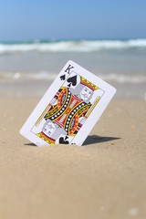King of clubs card, at the beach